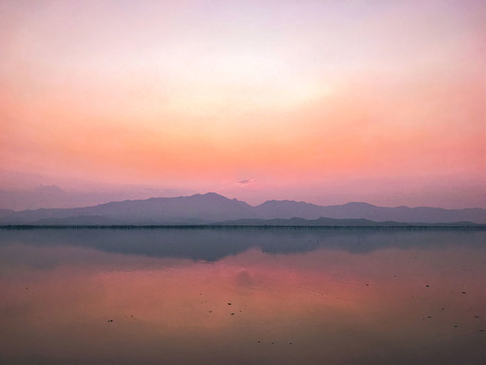 Scenic view of lake against romantic sky at sunset