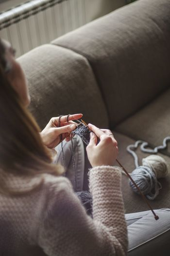 High Angle View Of Woman Knitting Wool While Sitting On Sofa At Home
