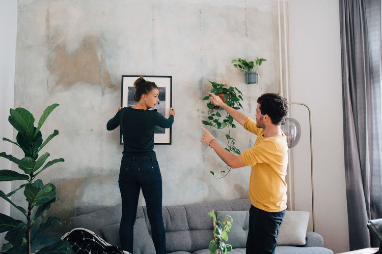 Friends standing on potted plant against wall