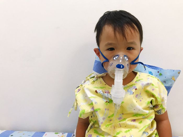 Portrait Of Cute Boy Wearing Oxygen Mask Against Wall At Hospital