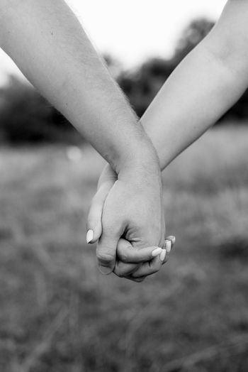 Close-up of bride and groom holding hands against lawn outdoors