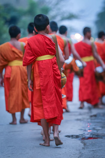 Buddhist Practice Novice Practitioner Novice Practitioner Of Buddhist Practice Belief Clothing Day Focus On Foreground Full Length Group Of People Men People Real People Rear View Red Religion Robe Spirituality Traditional Clothing Walking