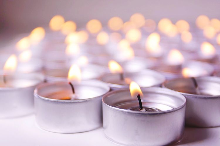 Burning tea light candles on table