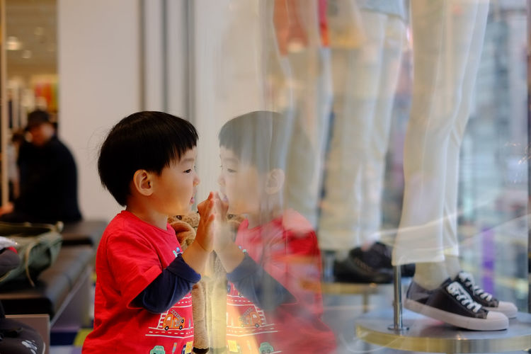 Side View Of Boy Looking At Mannequins On Window Display At Shopping Mall