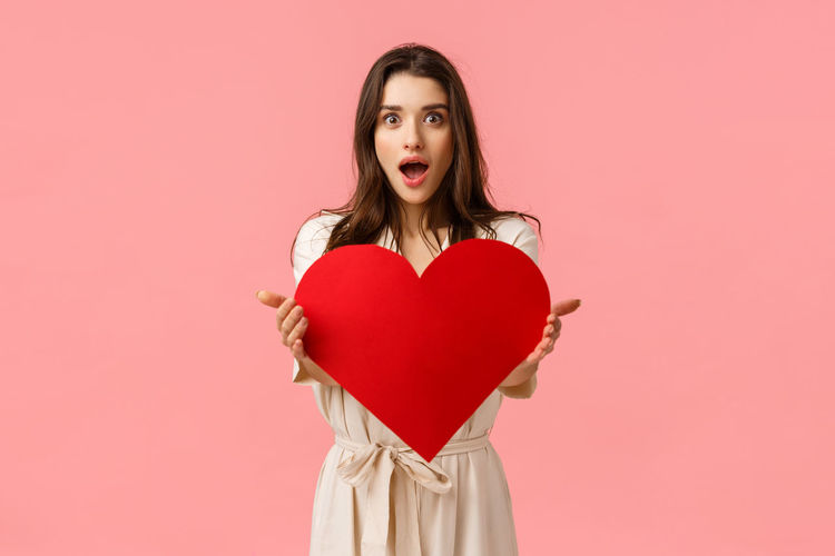 Portrait of woman with red heart shape against gray background