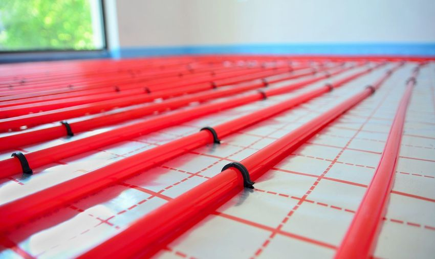 Water underfloor heating pipes on the silver reflective foil in house construction. Construction Flooring Home Red Floor Foil  Glowing Ground Heating House Interior Pipes Reflective Silver  System Underfloor Water