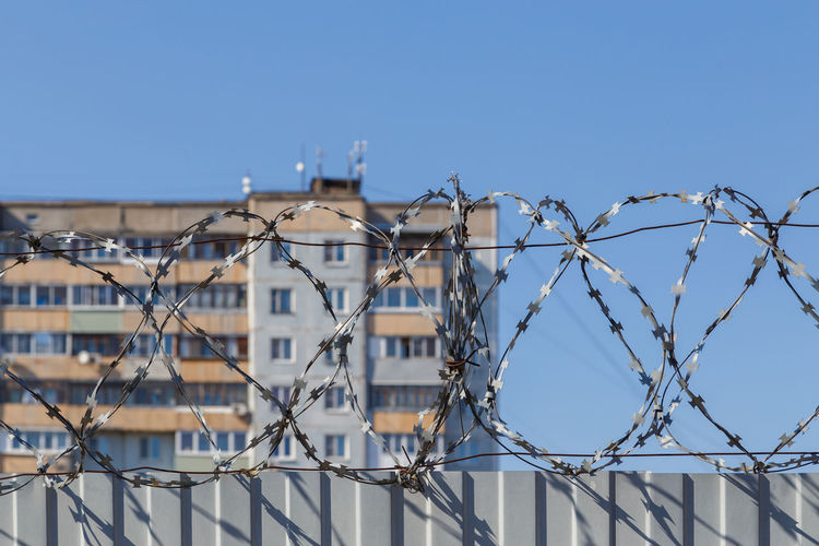 Residential multi-storey building behind a fence with barbed wire, concept of imprisonment