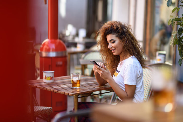 Young Woman Using Phone At Restaurant