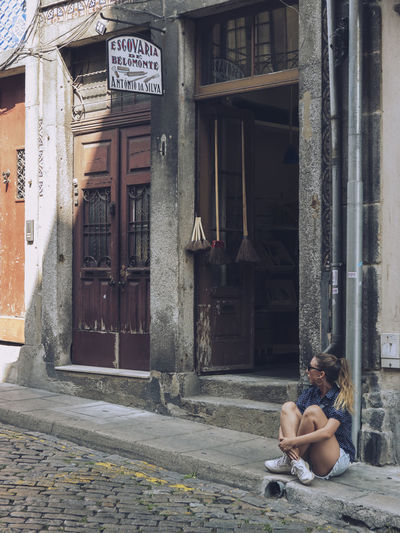 Woman sitting on street against building