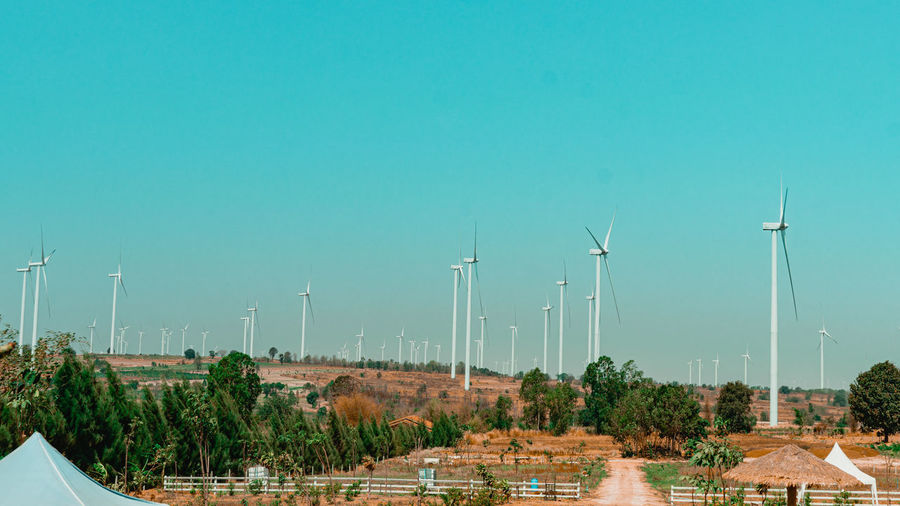 Panoramic view of wind turbines against sky