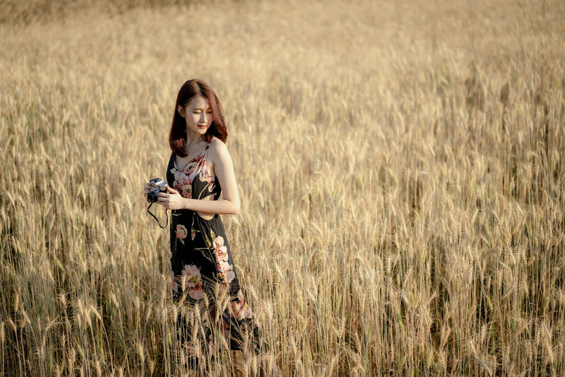 Young woman holding camera while standing amidst crops on agricultural field