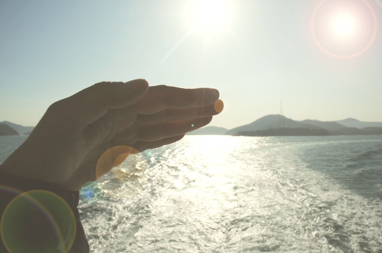 CLOSE-UP OF HAND BY SEA AGAINST CLEAR SKY
