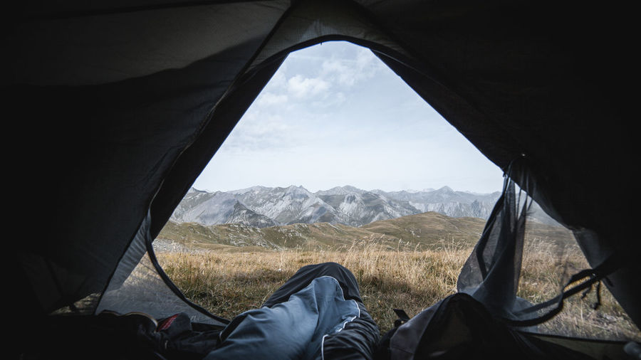 Low section of person in tent against mountains