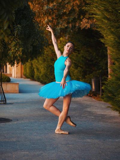 Ballet Dancer Dancing On Footpath Against Trees