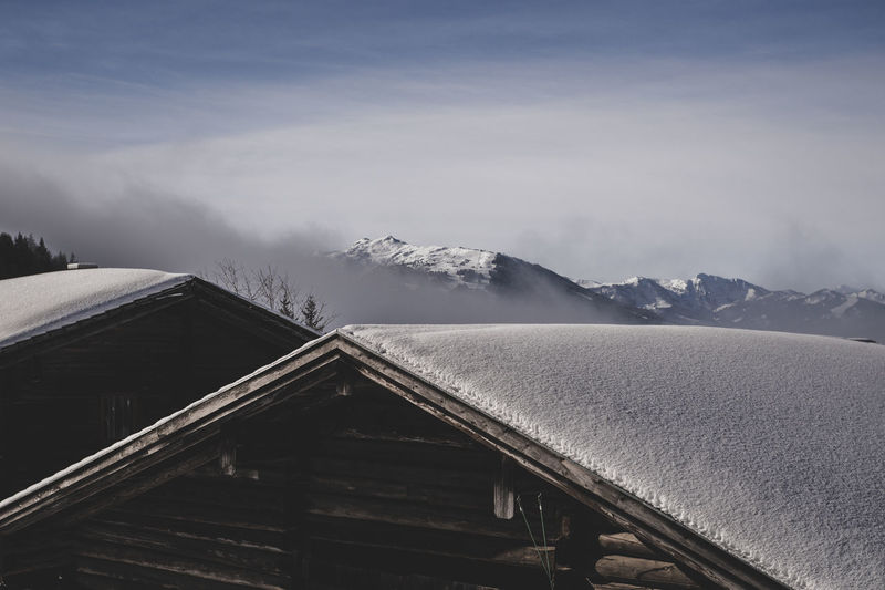 Scenic view of snowcapped mountains against sky and hut