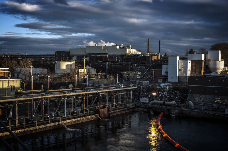 Factory by river against cloudy sky at dusk