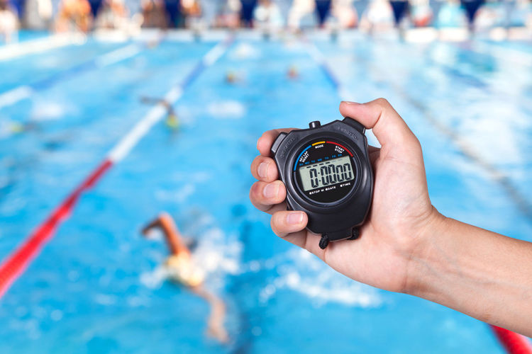 Cropped Image Of Coach Holding Stopwatch Against Swimming Pool
