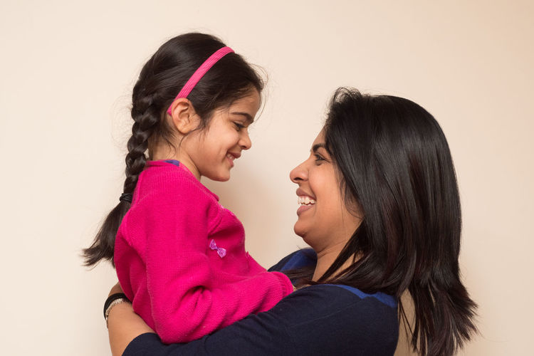 Happy mother carrying daughter against beige background