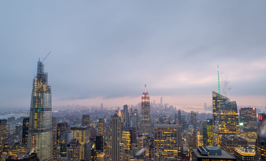 New york skyline from the top of the rock in rockefeller center at night with clouds in the sky