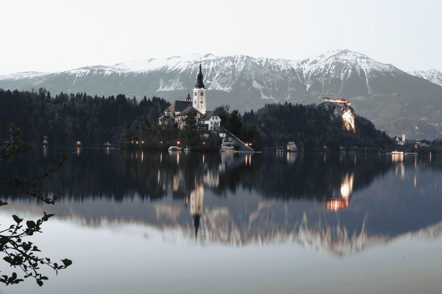Reflecting Lake Bled Slovenia Water Reflection Sky Lake Tree Plant Nature Beauty In Nature Scenics - Nature No People Mountain Tranquility Waterfront Clear Sky Travel Destinations Tranquil Scene Day Architecture Built Structure Outdoors