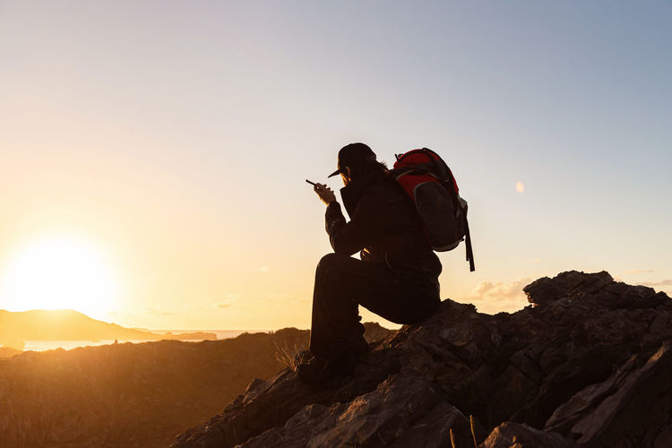 Man holding rock on mountain against sky during sunset
