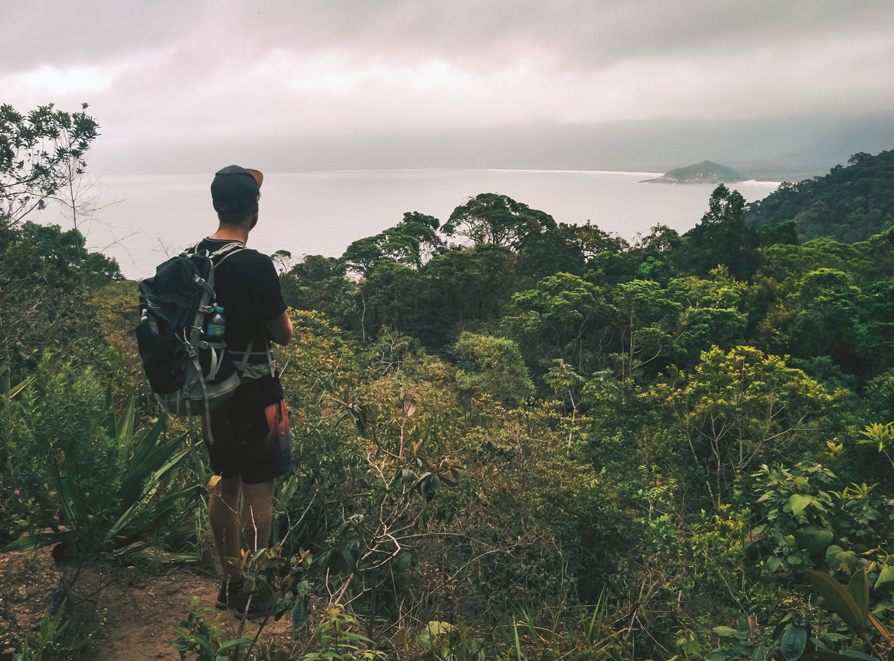Rear View Of Man With Backpack Looking At Sea While Standing On Mountain Against Cloudy Sky