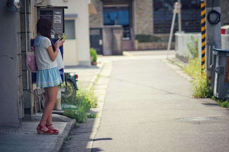 Young woman using phone while standing on footpath