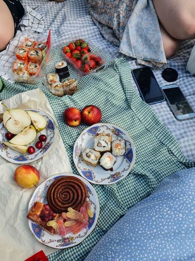 High angle view of hand holding fruit on table picnic on grass with flowers
