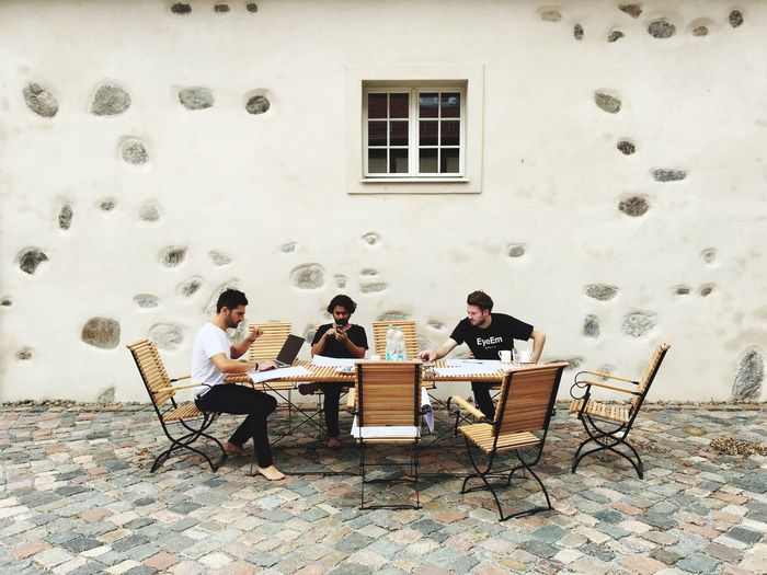 Three men sitting at outdoor table