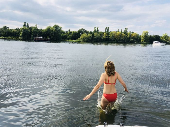 Rear view of woman jumping in lake