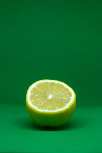 Close-up of lemon slice over green background