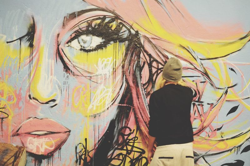 Rear view of man drawing graffiti on wall
