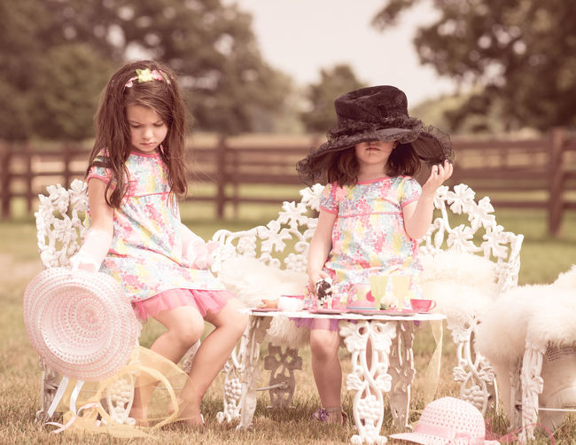 Girls sitting on chairs at table on field