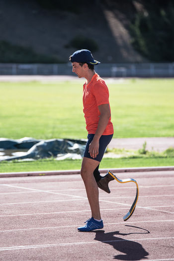 Side view of young athlete with prosthetic leg standing at sports track