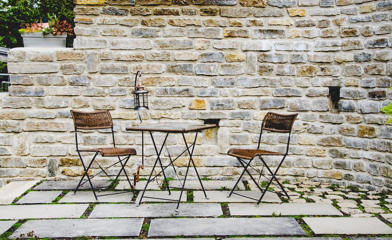 seat, wall, wall - building feature, chair, architecture, brick, brick wall, no people, built structure, table, absence, day, stone wall, potted plant, empty, outdoors, nature, relaxation, plant, footpath