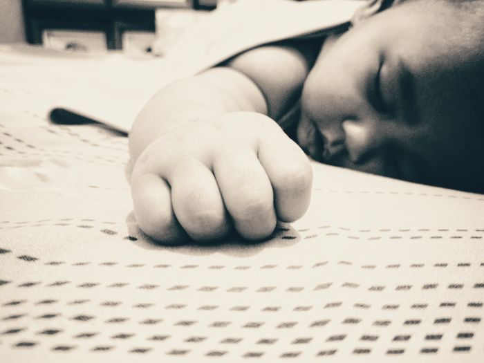 Close-up of baby girl sleeping on bed