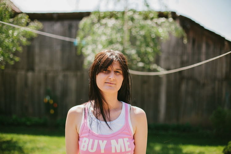 Portrait of woman wearing tank top with buy me written standing outdoors