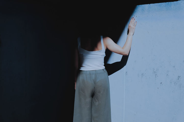 Rear View Of Woman Standing By Wall In Darkroom