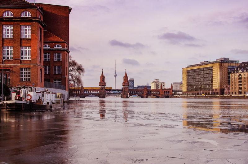 Boat On Frozen Lake Against Oberbaum Bridge In City