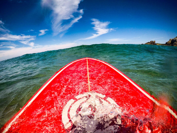 Red surfboard in sea against sky on sunny day