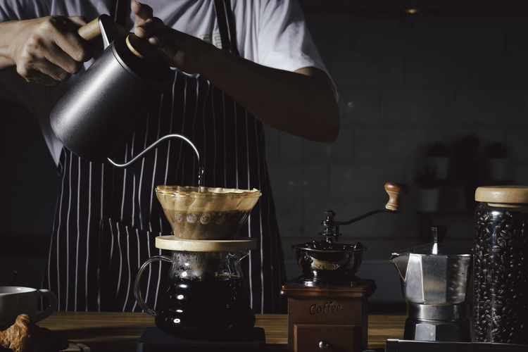Man pouring coffee in cup