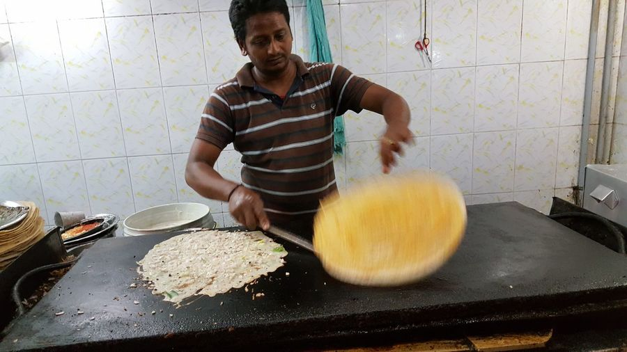 Tilt Shot Of Chef Flipping Thosai At Commercial Kitchen