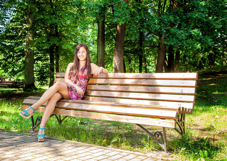 Portrait of young woman sitting on bench at park