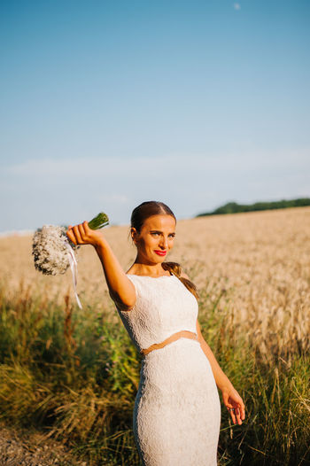 Portrait of smiling bride with bouquet standing on farm
