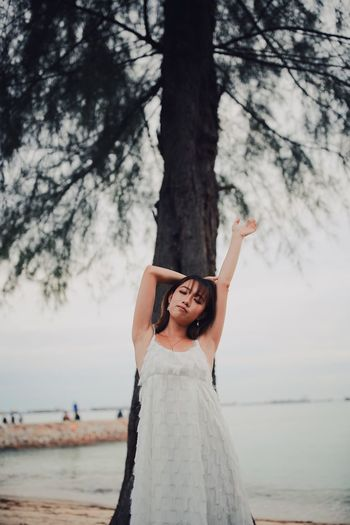 Portrait of young woman standing with arm raised against tree