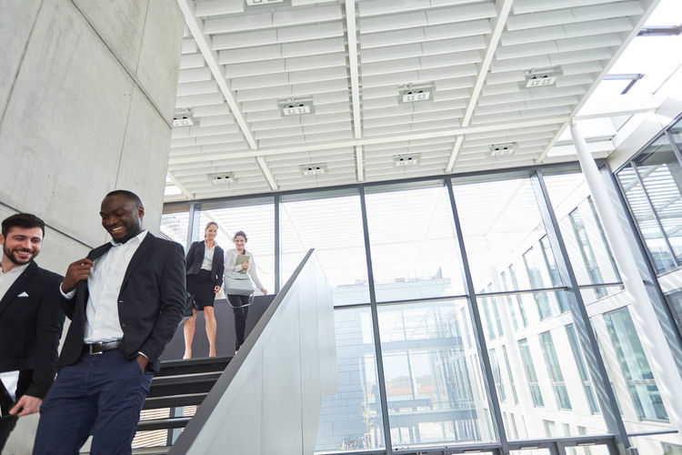 Low angle view of people standing in modern building