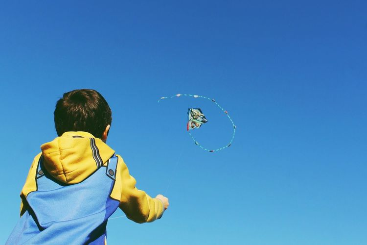 Low angle view of boy flying kite against clear blue sky