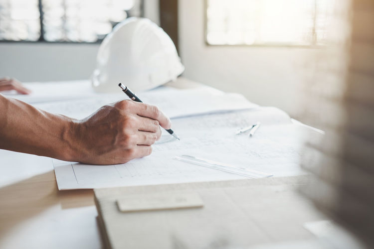 Cropped hand of engineer drawing blueprint at desk in office