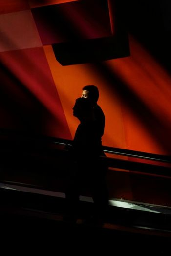 Low angle view of silhouette man standing against wall