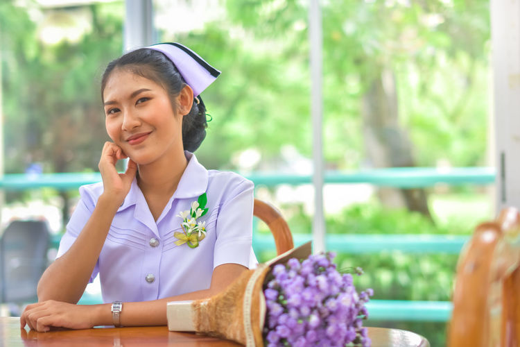 Smiling Young Nurse Sitting At Table Against Window